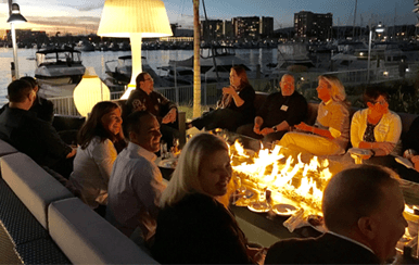 Roundtable group sitting around a fire at the marina at night